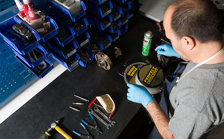 man inspecting perfect descent auto belay on work bench