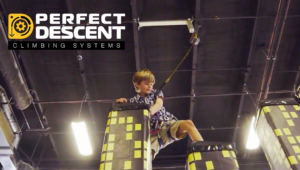 Young boy climbing with a Perfect Descent Auto Belay at a rock climbing gym