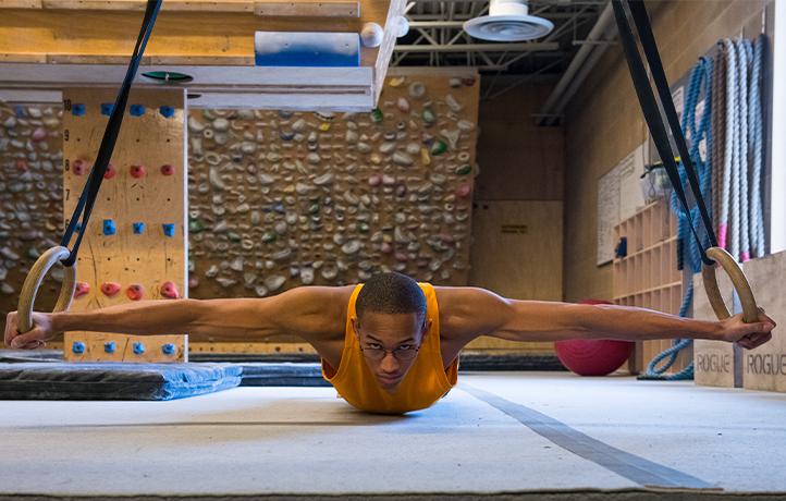 Kai Lightner training on rings in climbing gym