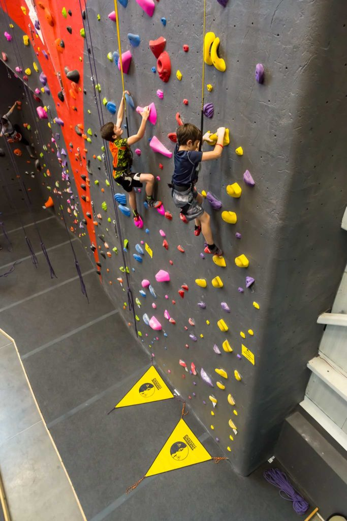 children-climbing-gym-side-by-side-on-perfect-descent-auto-belays