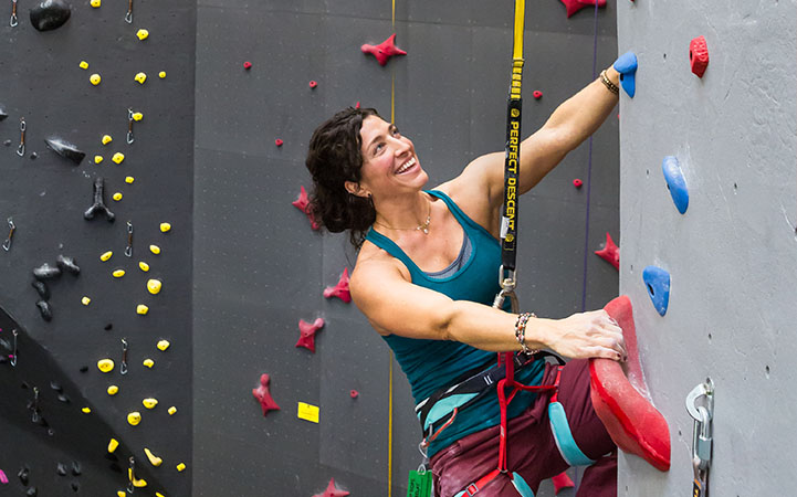 woman-climbing-indoors-smiling-on-perfect-descent-auto-belay