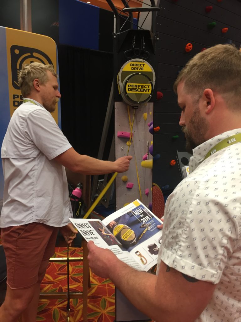 Customers checking out the Perfect Descent Auto Belays at the CWA booth