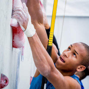 young man clipped into perfect descent auto belay for competition