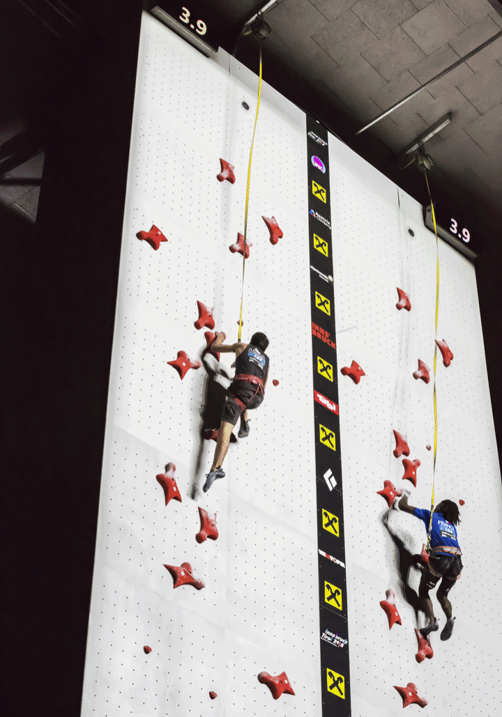 Speed climbers racing side by side up a speed climbing wall at the 2018 world climbing championship