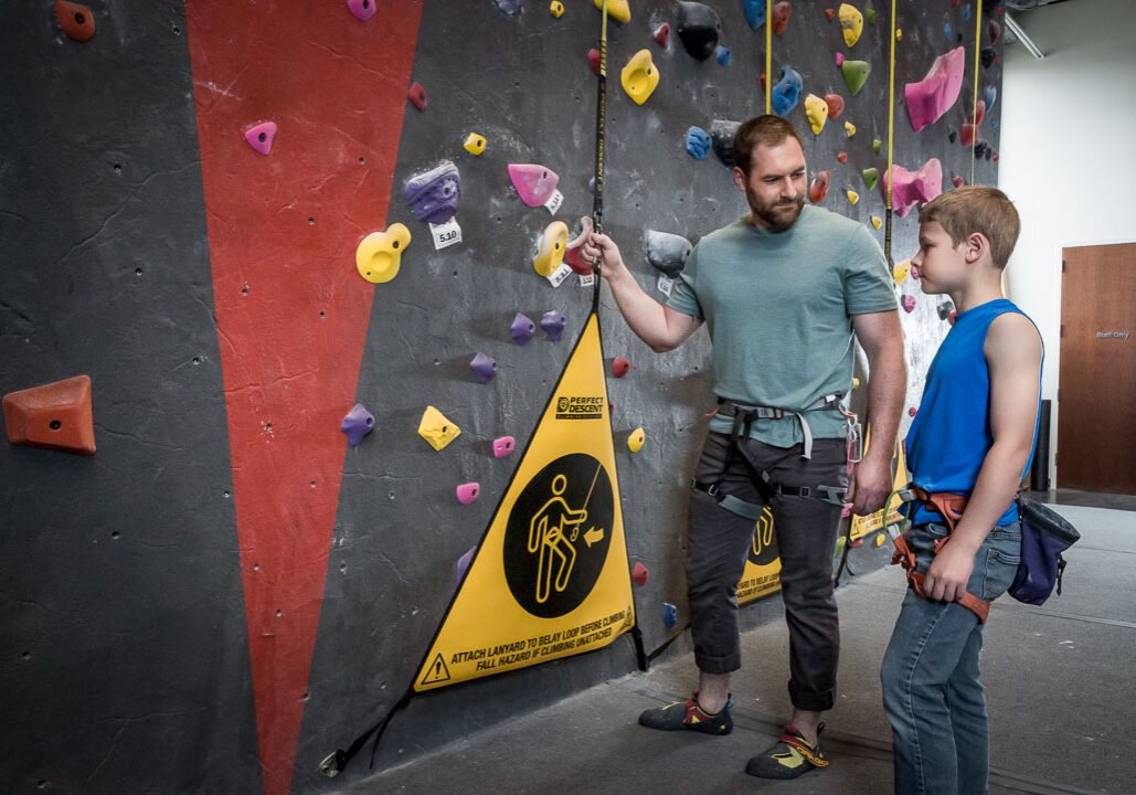 son and father at a rock climbing gym using perfect descent auto belays