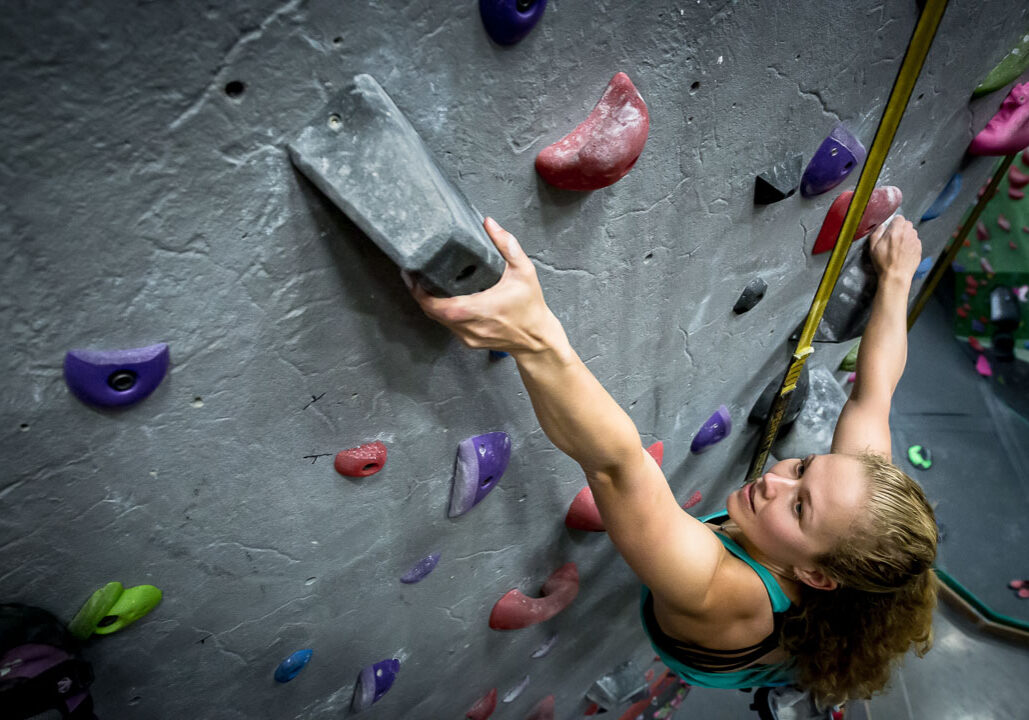 woman rock climbing in a gym on a perfect descent auto belay
